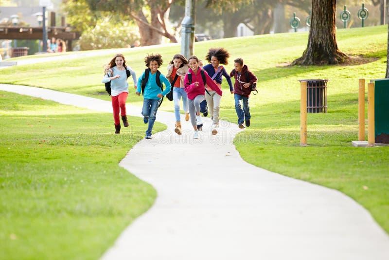 Gruppe Kinder, die entlang Weg in Richtung zur Kamera im Park laufen lizenzfreie stockbilder