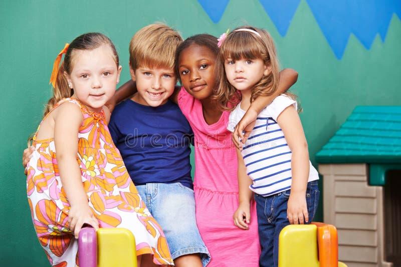 Gruppe Kinder, die im Kindergarten umfassen lizenzfreie stockfotografie