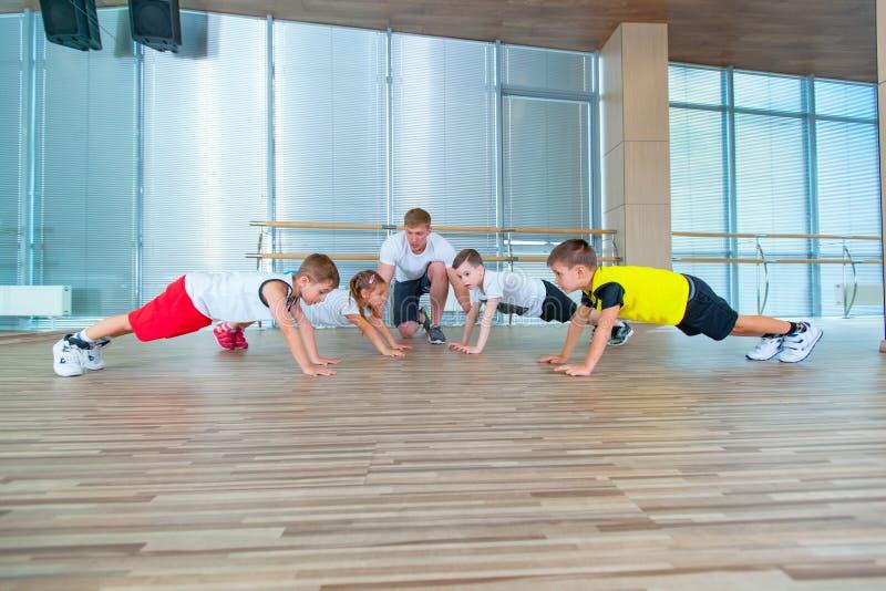 Gruppe Kinder, die Kindergymnastik in der Turnhalle mit Lehrer tun Glückliche sportliche Kinder in der Turnhalle Stangenübung pla lizenzfreie stockbilder