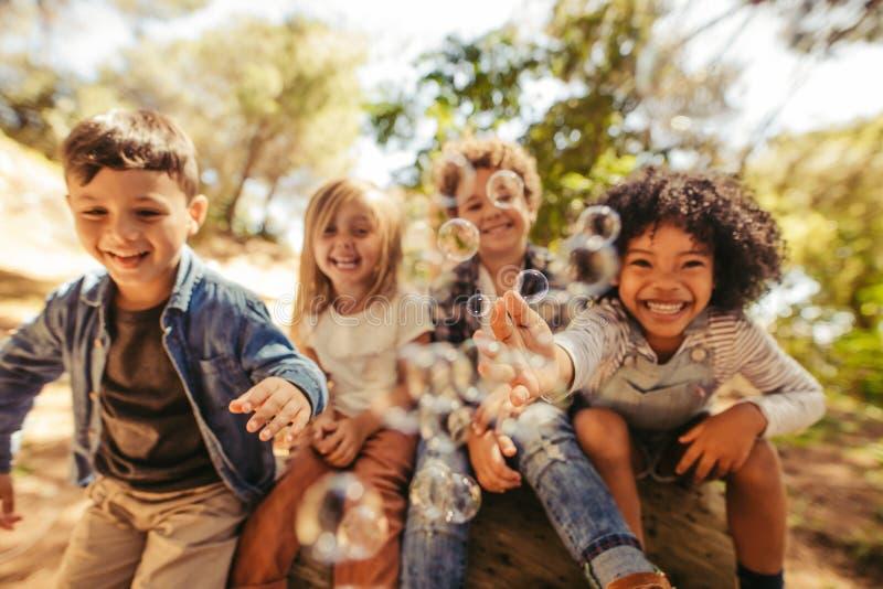 Gruppe Kinder, die mit Seifenblasen spielen stockbilder