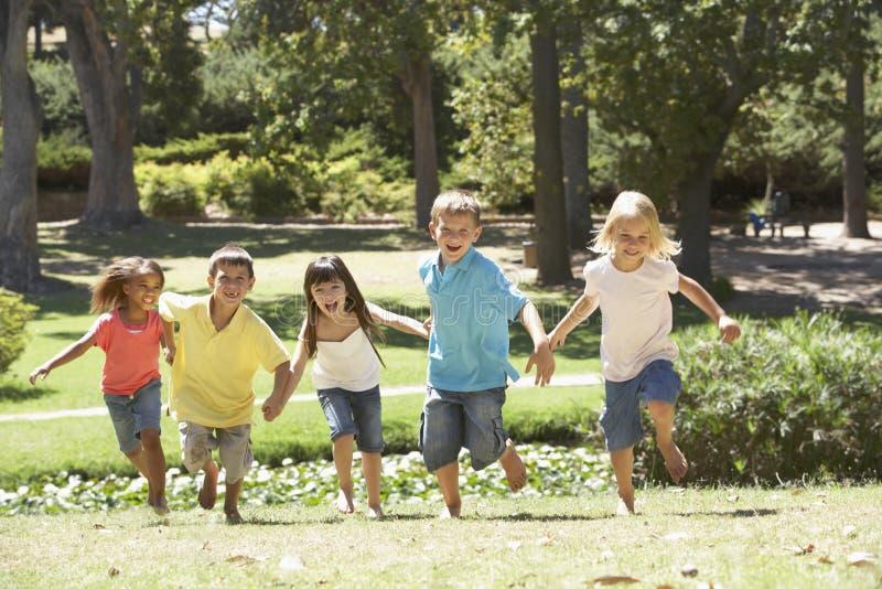 Gruppe Kinder, die in Park laufen stockbilder