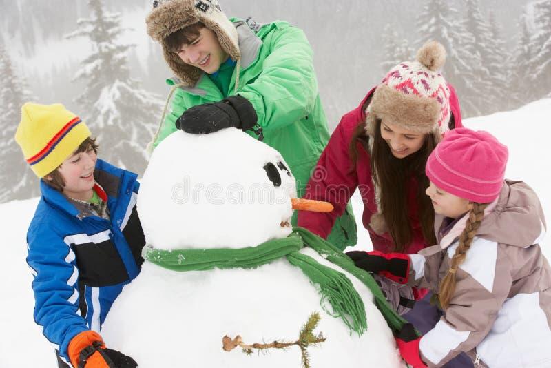Gruppe Kinder, die Schneemann am Ski-Feiertag aufbauen lizenzfreie stockfotografie