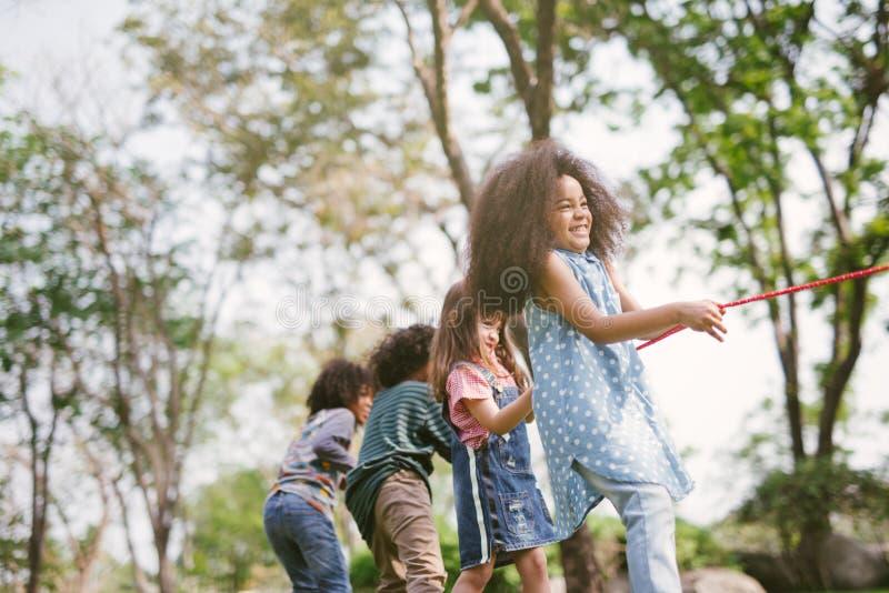 Gruppe Kinder, die Tauziehen am Park spielen stockbild