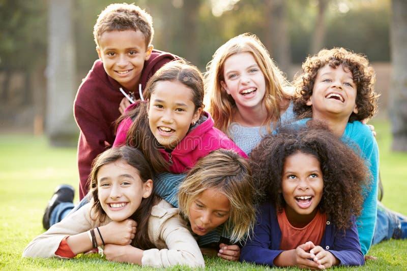 Gruppe Kinder, die zusammen auf Gras im Park liegen stockfotos