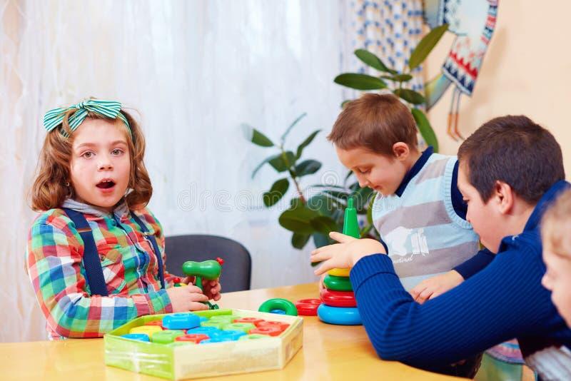 Gruppe Kinder, die zusammen in Kindertagesstätte für Kinder mit speziellem Bedarf spielen stockfotografie