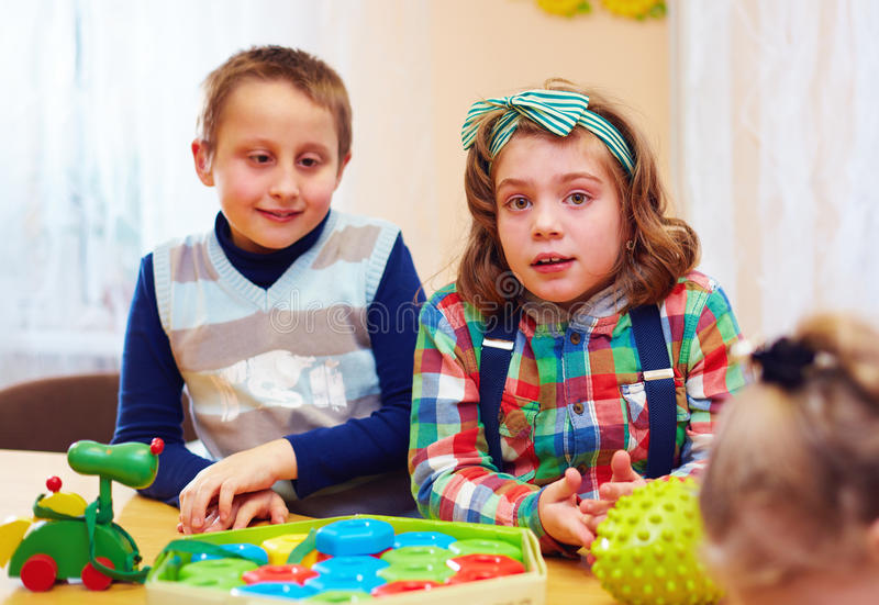 Gruppe Kinder, die zusammen in Kindertagesstätte für Kinder mit speziellem Bedarf spielen lizenzfreies stockbild