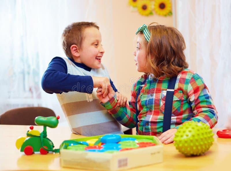 Gruppe Kinder, die zusammen in Kindertagesstätte für Kinder mit speziellem Bedarf spielen lizenzfreies stockfoto