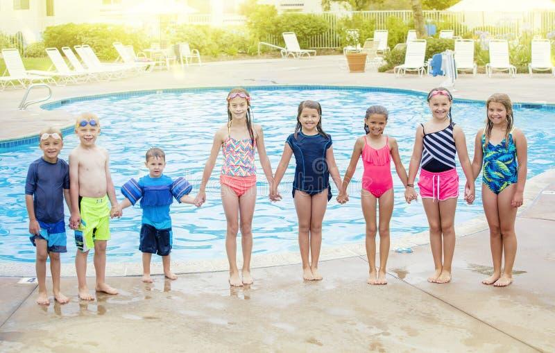 Gruppe Kinder, die zusammen am Swimmingpool spielen stockfotos