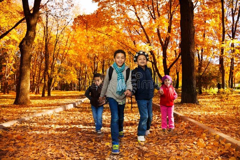 Gruppe Kinder gehen zur Schule im Herbstpark lizenzfreie stockbilder