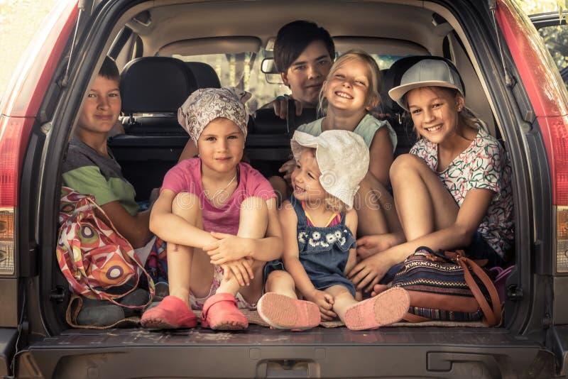 Gruppe Kinder im Familienautokofferraumgepäck gehend zur Autoreise im Familienauto, das Kinderzusammengehörigkeitsfreundschaft sy stockfotografie