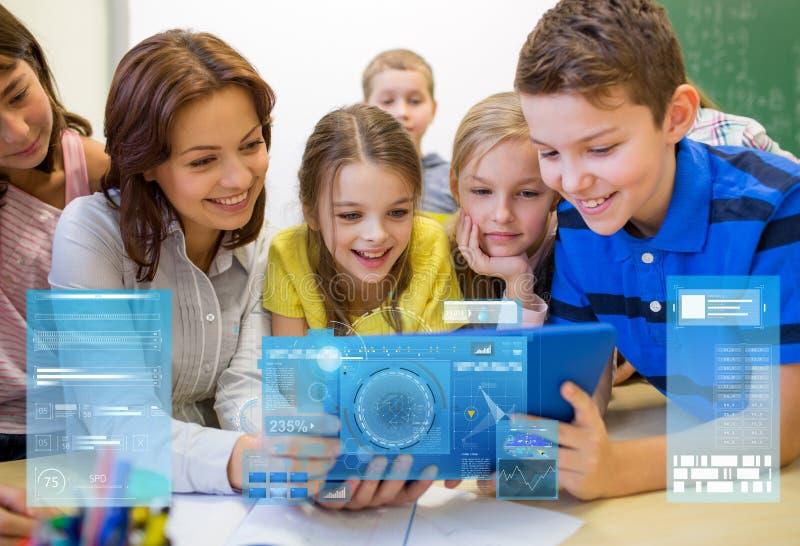 Gruppe Kinder mit Lehrer- und Tabletten-PC in der Schule stockfotografie