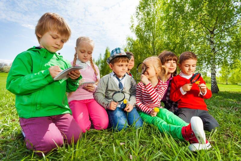 Gruppe Kinder sitzen auf dem Gebiet mit Vergrößerungsglas stockbilder