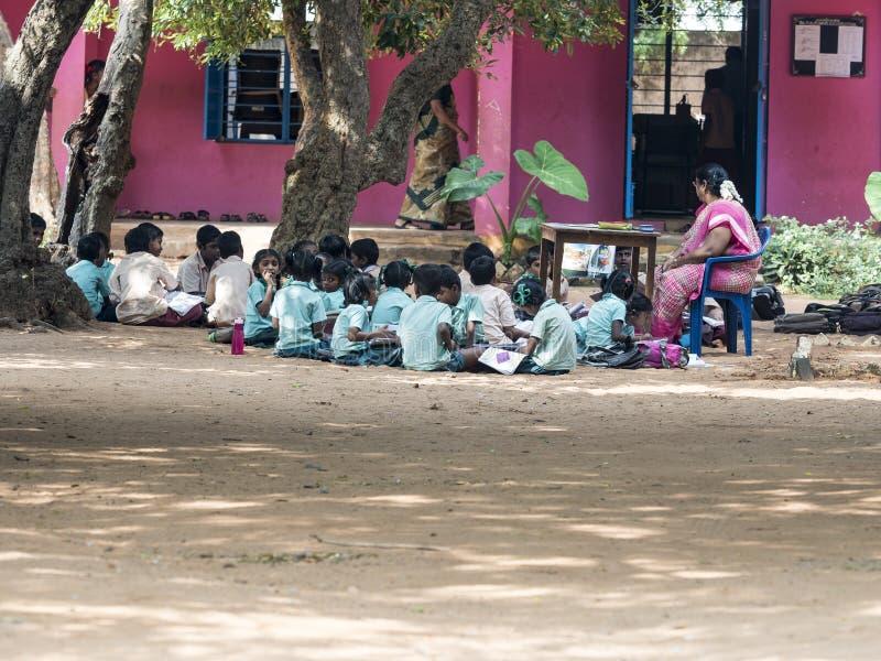 Gruppe Kinderfreundmädchen-Jungenmitschüler, die mit dem Buch in der Schule sitzt auf Spielplatz des Bodens im Freien studieren lizenzfreies stockfoto