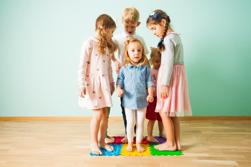 Gruppe Kinderstände auf dem Massieren von Matten stockfotografie
