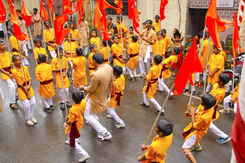 Gruppe kleine Jungen, tanzend mit Flaggen, während Ganapti-Prozession, Ganapati-Festival stockbilder