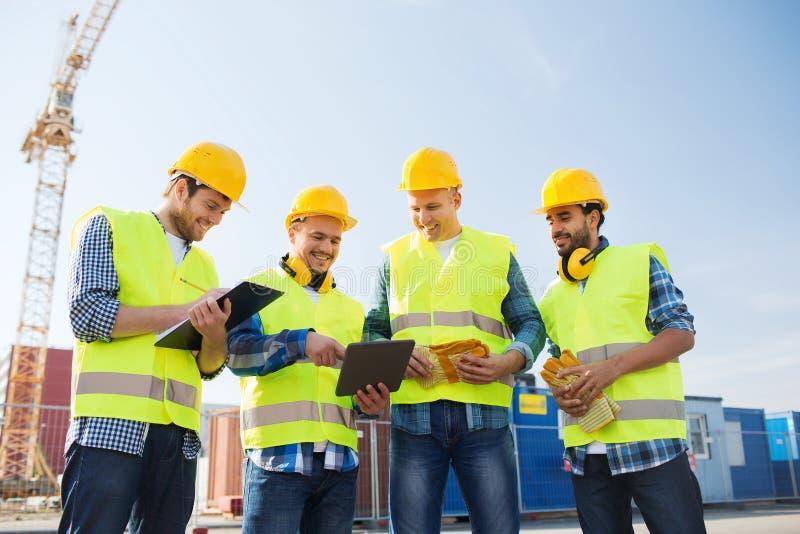 Gruppe lächelnde Erbauer mit Tabletten-PC draußen lizenzfreie stockfotografie