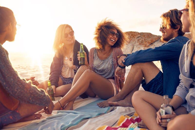 Gruppe lächelnde Freunde, die auf dem Strand kühlen lizenzfreies stockfoto