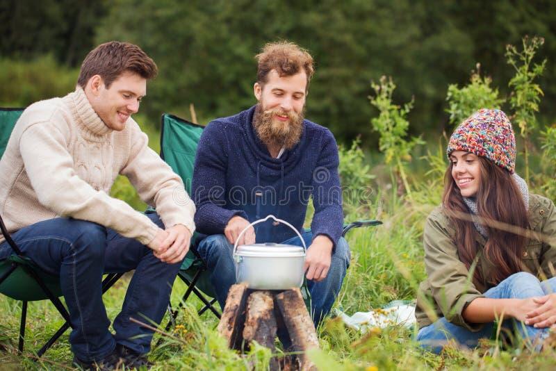 Gruppe lächelnde Freunde, die draußen Lebensmittel kochen lizenzfreie stockfotografie