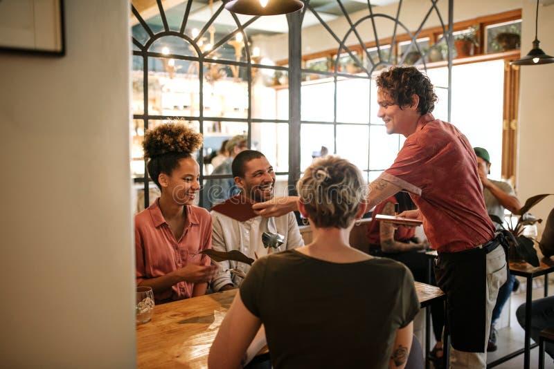 Gruppe lächelnde Freunde, die Lebensmittel von einem Bistrokellner bestellen lizenzfreie stockfotografie