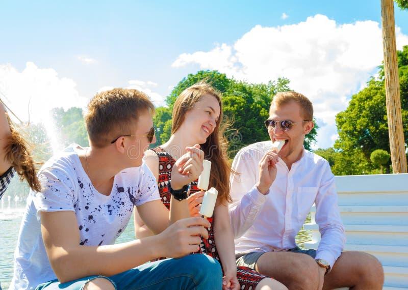 Gruppe lächelnde Freunde mit Eiscreme draußen stockbild