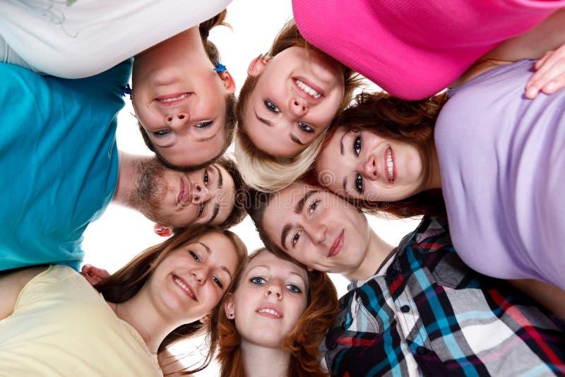 Gruppe lächelnde Freunde mit ihren Köpfen zusammen lizenzfreie stockfotos