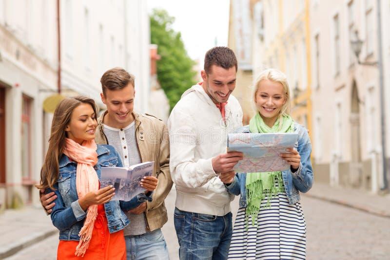 Gruppe lächelnde Freunde mit Stadtführer und -karte stockfotos