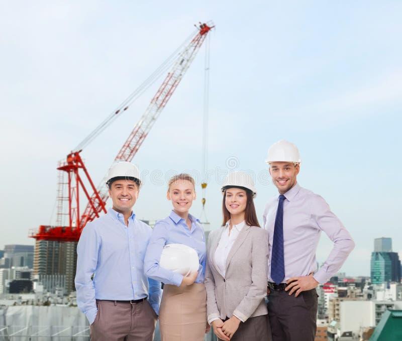Gruppe lächelnde Geschäftsmänner in den weißen Sturzhelmen lizenzfreie stockbilder