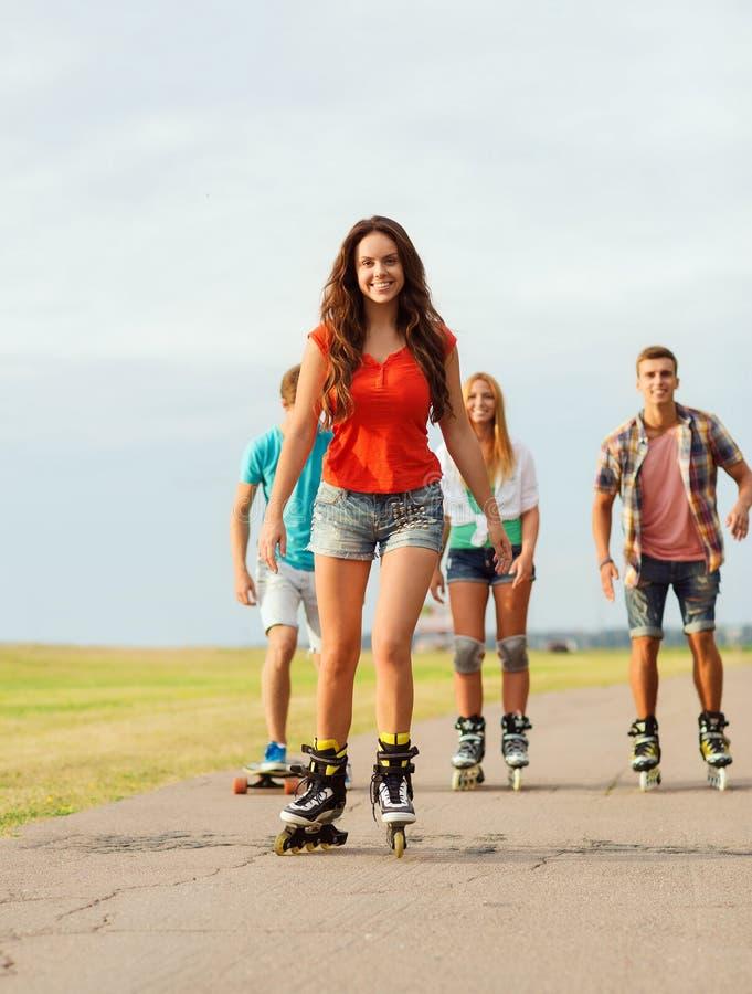 Gruppe lächelnde Jugendliche mit läuft Rollschuh stockfotos