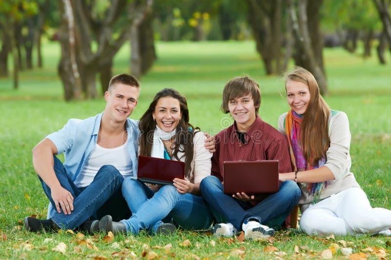 Gruppe lächelnde junge Kursteilnehmer draußen stockfotografie