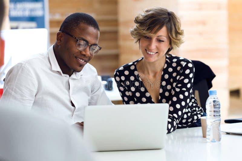 Gruppe lächelnde junge Wirtschaftler, die mit Laptop auf coworking Platz arbeiten stockfotos