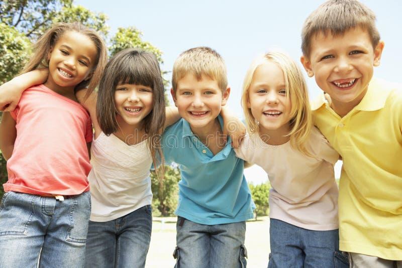 Gruppe lächelnde Kinder, die im Park sich entspannen lizenzfreies stockfoto