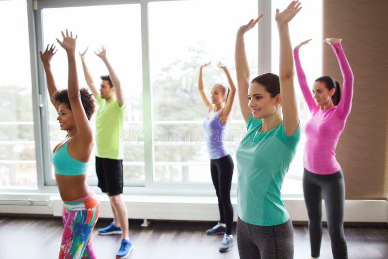 Gruppe lächelnde Leute, die in Turnhalle oder in Studio tanzen stockbild