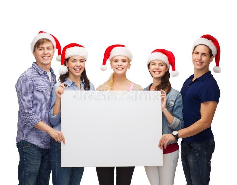 Gruppe lächelnde Studenten mit weißem leerem Brett stockbild