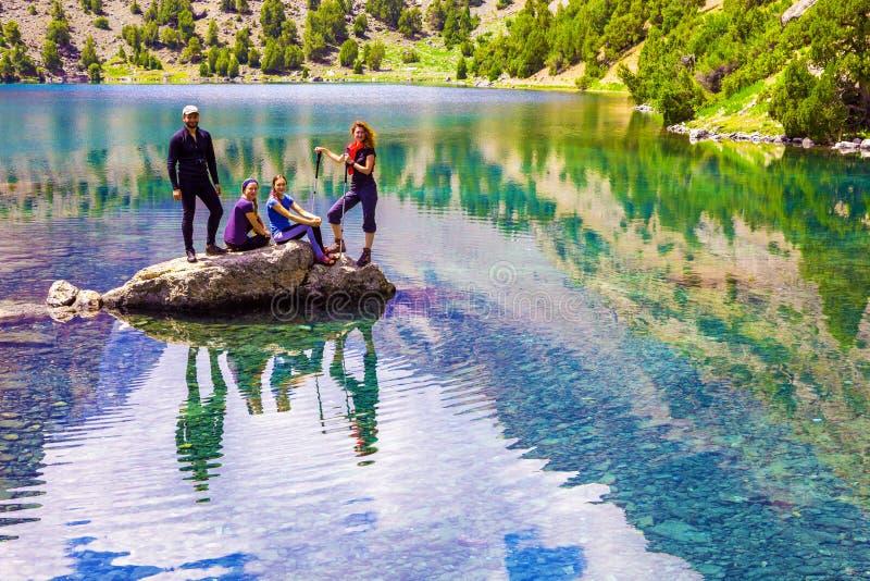 Gruppe lächelnde Wanderer auf Felsen am Mountainsee lizenzfreies stockfoto