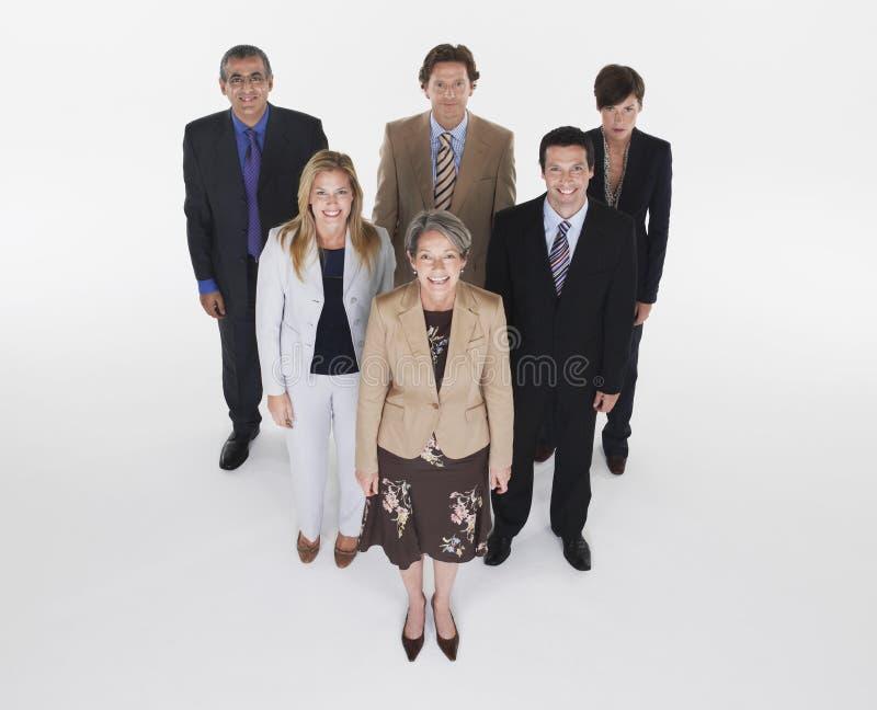 Gruppe lächelnde Wirtschaftler in der Dreieck-Bildung stockfotos