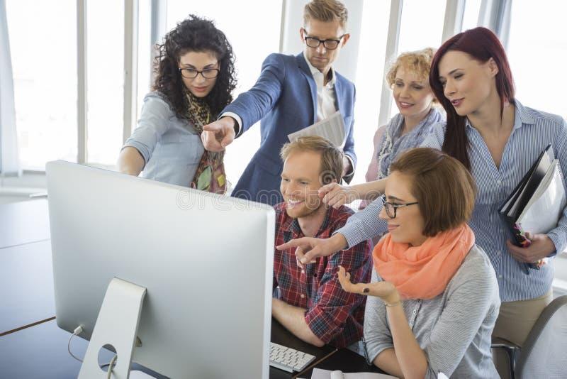 Gruppe lächelnde Wirtschaftler, die zusammen Computer im Büro verwenden lizenzfreie stockbilder