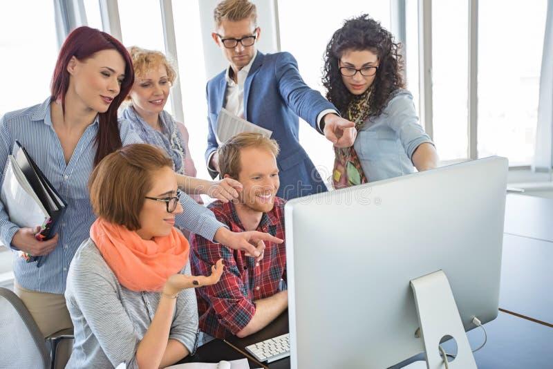 Gruppe lächelnde Wirtschaftler, die zusammen Computer im Büro verwenden stockbild