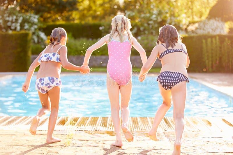 Gruppe Mädchen, die in Swimmingpool im Freien springen stockbild