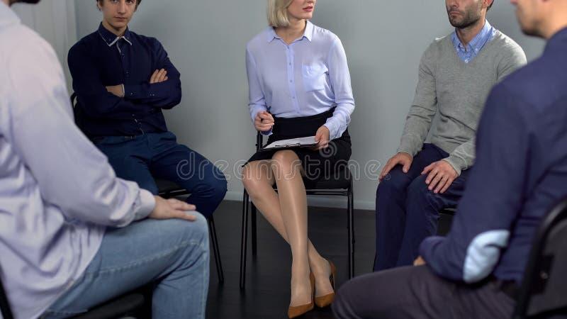 Gruppe Männer, die Arbeitskonflikt mit Kollegen bei der Psychotherapiesitzung besprechen lizenzfreies stockbild