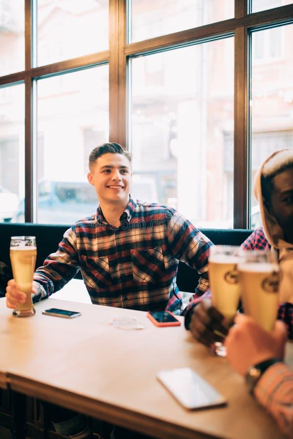 Gruppe Männer, die Bier trinken und Gespräch in der Kneipe haben Treffen des gemischtrassigen Studenten in der Kneipe lizenzfreies stockbild