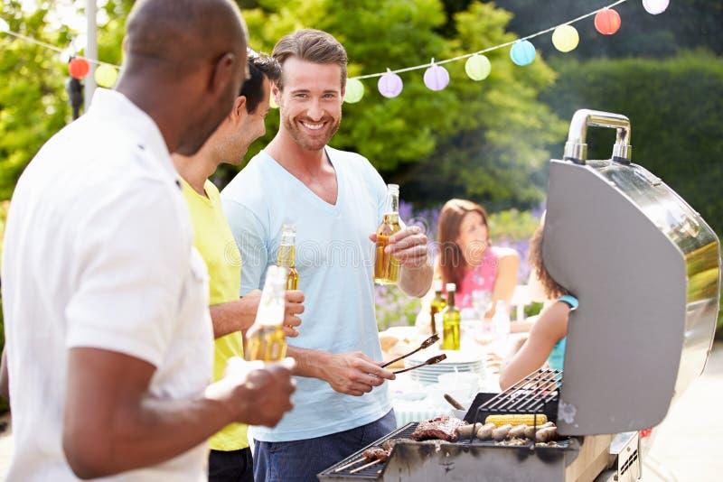 Gruppe Männer, die zu Hause auf Grill kochen lizenzfreie stockfotos