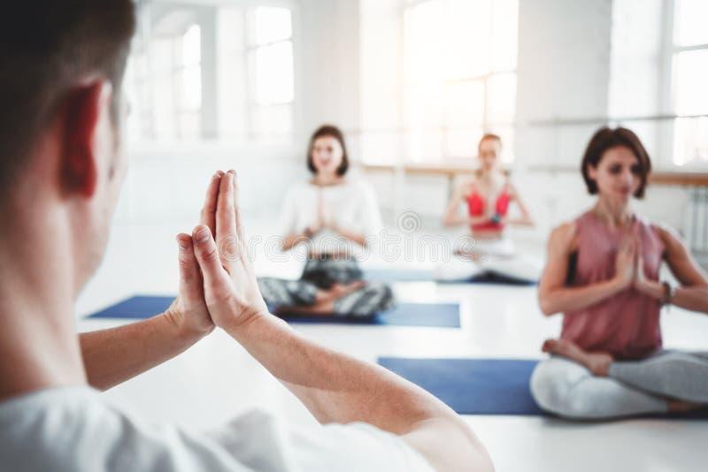 Gruppe Männer und Frauen, die Eignungstraining in der Klasse aufwärmen und tun Junge aktive Leute tun Yoga zusammen stockfoto
