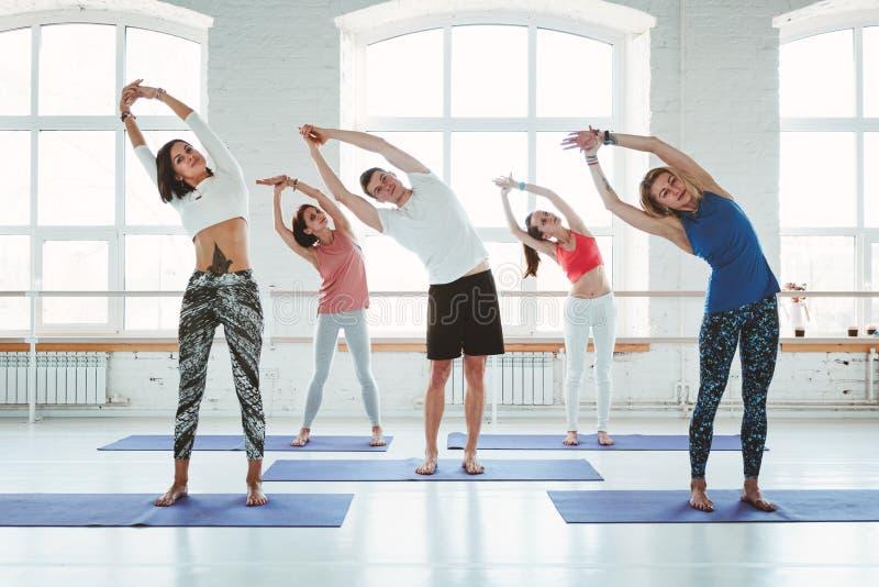 Gruppe Männer und Frauen, die Eignungstraining in der Klasse aufwärmen und tun Junge aktive Leute tun Yoga zusammen lizenzfreies stockbild