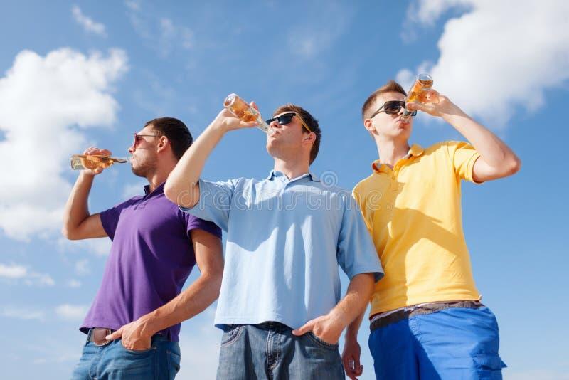 Gruppe männliche Freunde mit Flaschen Bier lizenzfreie stockfotografie