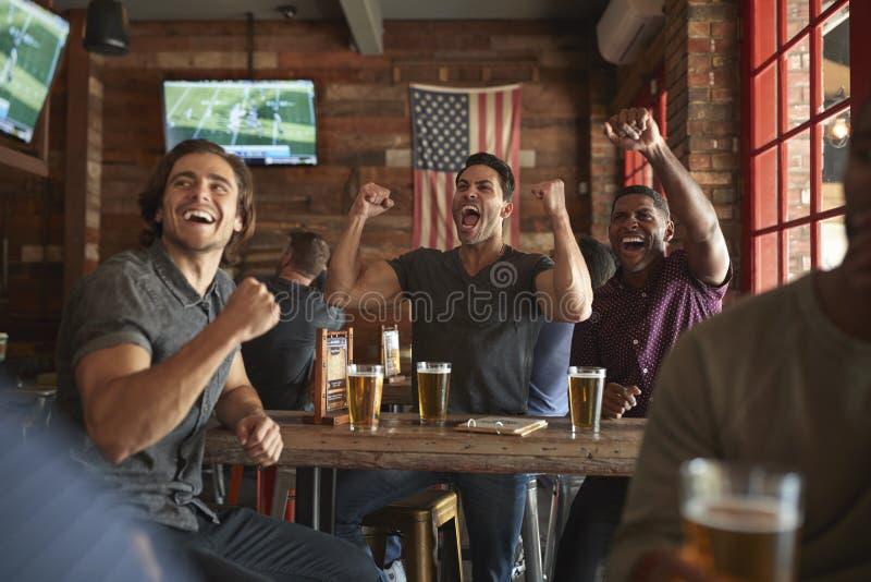 Gruppe m?nnliche Freunde, die w?hrend feiern, Spiel auf Schirm im Sportbar aufpassend lizenzfreie stockfotos