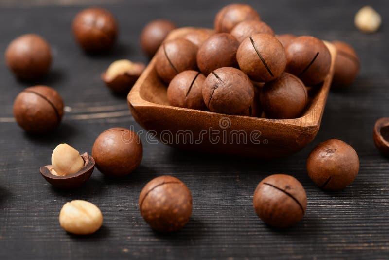 Gruppe Macadamianüsse auf schwarzem Holztisch lizenzfreies stockbild