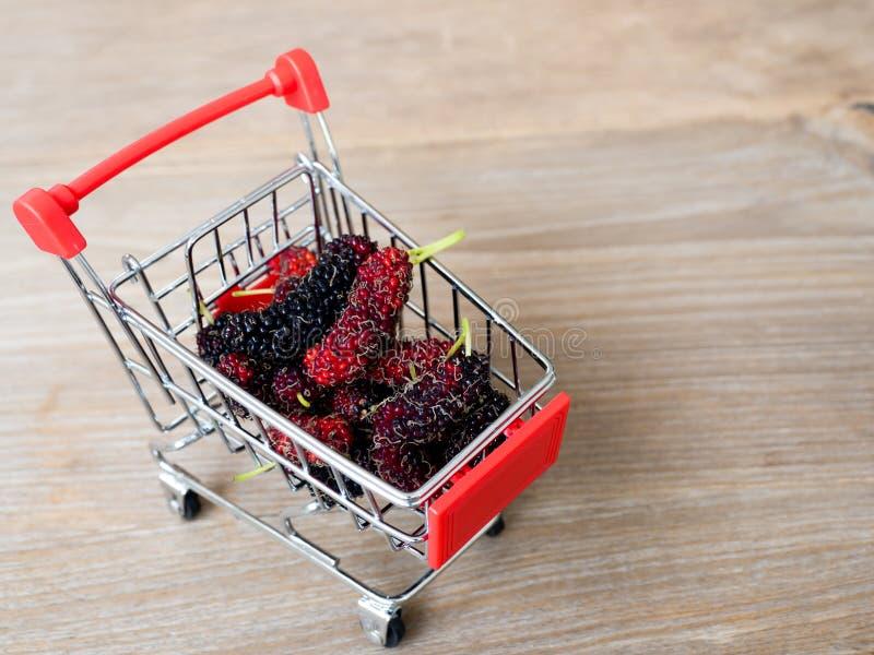 Gruppe Maulbeeren im roten Warenkorb auf Holztisch Maulbeere dieses eine Frucht und kann herein gegessen werden haben eine rote u stockfoto
