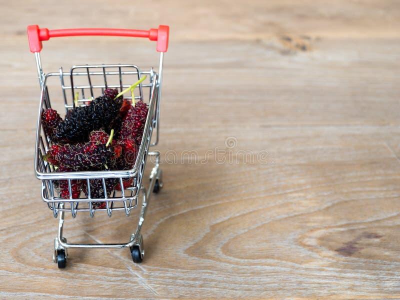 Gruppe Maulbeeren im roten Warenkorb auf Holztisch Maulbeere dieses eine Frucht und kann herein gegessen werden haben eine rote u lizenzfreie stockfotografie