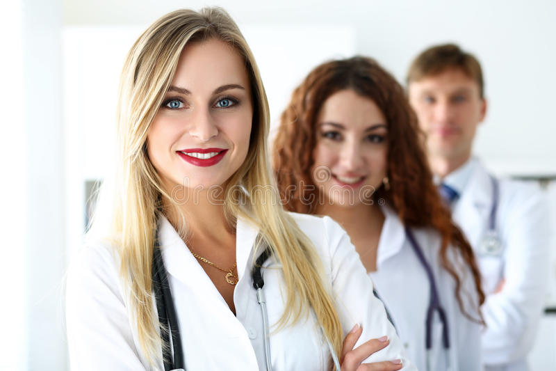 Gruppe Mediziner, die stolz in der Reihe aufwerfen und in camera schauen stockfotografie