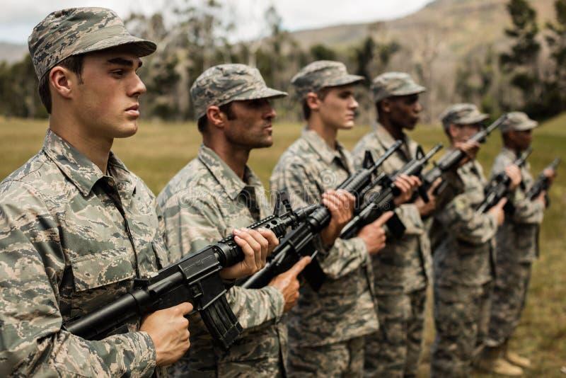 Gruppe Militärsoldaten, die mit Gewehren stehen stockbild